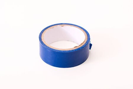 Insulating tape isolated on a white background, blue spool of adhesive electrical tape. Insulating tape for wires, universal repair material. Stock Photo