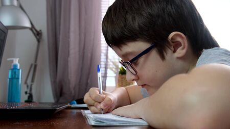 A boy, schoolboy sitting by the table, desk with laptop and doing homework at home, e-learning, distant lesson and online education concept. Stock Photo