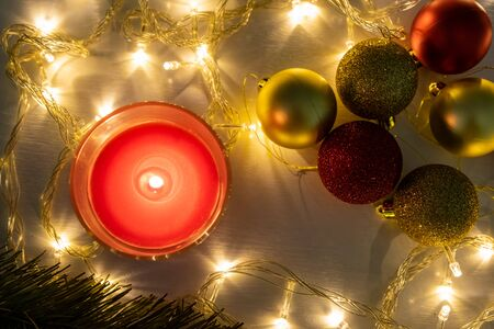 Red christmas candle, burning candle fire on a table with holiday garland and pine tree decorations and balls, top view.
