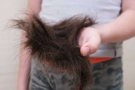 A boy holding a pile of his hair as a result of the haircut, homemade hairstyling and barber, lots of cutted hair in hands.