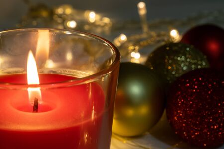 Red christmas candle, burning candle fire on a table with holiday garland and pine tree decorations and balls.