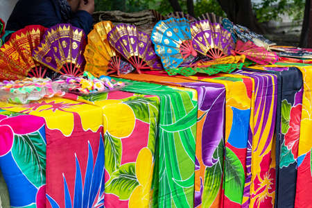 Yogyakarta, Indonesia - August 02, 2019: Woman selling various batik cloth, textyle. Traditional colorful indonesian sarong for sale at market..