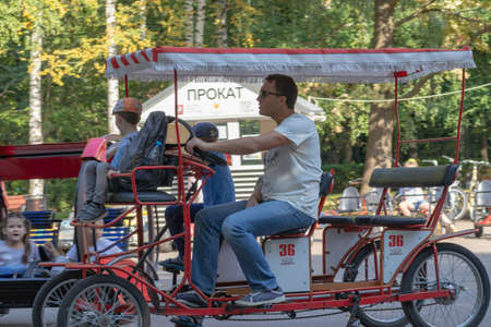 Moscow, Russia - Septmber 01, 2019: A man and a child riding car with pedals in a city park in summer, sport vehicles and equipment for rent as outdoor activity.