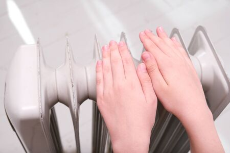 A child warming hands above portable oil heater, autumn and winter house heating.