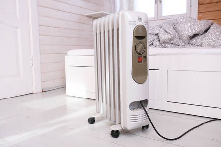 Oil-filled electrical mobile radiator heater for home heating and comfort control in the room in a wooden country house. Stock Photo