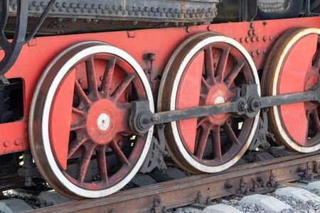 Red wheels of a vintage steam train locomotive close up, detail of a train of great world war times.