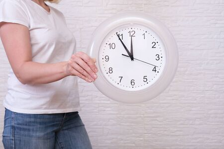 Woman holding clock showing five minutes to twelve, deadline and urgent work concept.