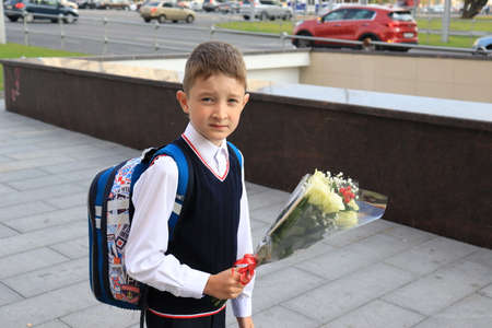 Moscow, Russia - September, 1 2017: The first call, a boy going to school for the first time on September 1 with flowers in hands, Day of Knowledge in Russian school.Traditional form of education. 報道画像