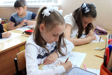Moscow, Russia - September 1, 2017: Schoolgirls sitting at the desk in class at school, traditional learning, offline education form, Day of knowlege in Russian school. 報道画像