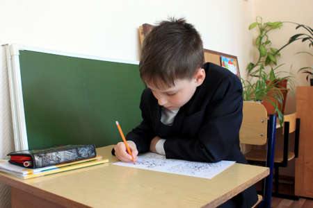Moscow, Russia - September 1, 2017: Schoolboy, pupil sitting at the desk in class at school, traditional learning, offline education form, Day of knowlege in Russian school.