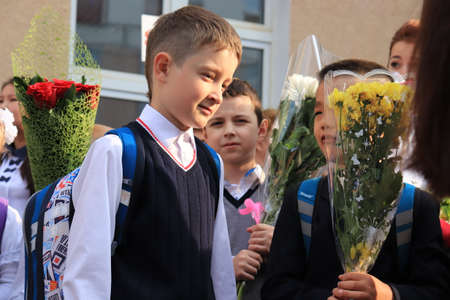 Moscow, Russia - September, 1 2017: The first call, children go to school for the first time on September 1, Day of Knowledge in Russian school. School line is in schoolyard with first-grade pupils.
