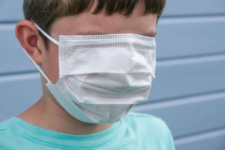 A funny view of a boy wearing white protective surgical medical mask, covering even his eyes to prevent infection during epidemia, pandemia prank rofl joke