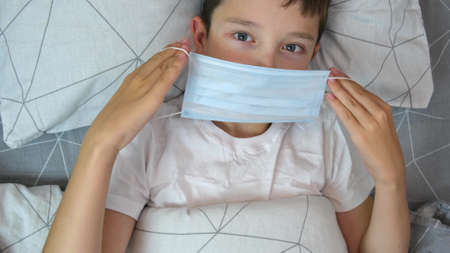 A portrait of a sick caucasian boy lying in bed and putting on a medical protective mask, illness and flu concept. Reklamní fotografie
