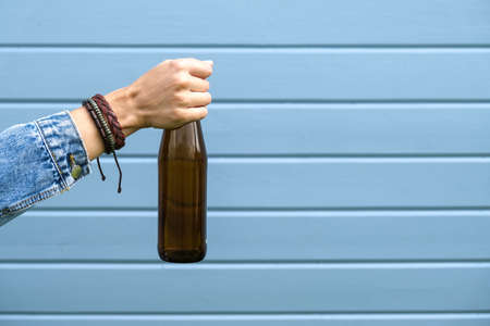 A female hand dressed punk, infirmal holding a bottle of beer against blue wooden plank wall, abuse and alcohol addiction concept, copy space. Reklamní fotografie