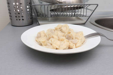 Traditional tasty hot boiled russian pelmeni, ravioli, dumplings with meat on white ceramic plate in kitchen interior after cooking.