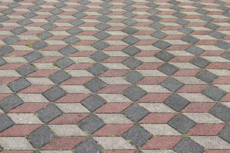 Urban walkway made of red, yellow rhombus and gray bricks, paving slabs background.