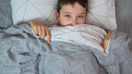 Portrait of a scared boy in bed getting out from under the cover and covering his face with blanket, children kid fears concept.