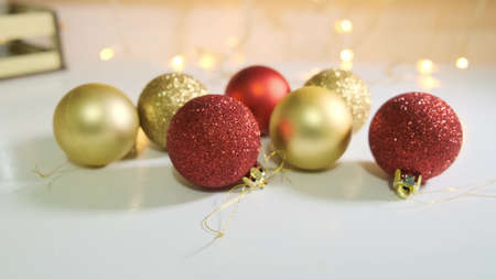 Red and golden christmas balls decorated with glitter close up on white table with a garland on backdrop.