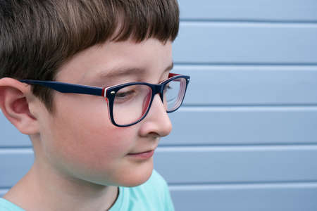 A portrait of a boy wearing glasses against gray blue plank painted wall with copy space, myopia, astigmatism and ophthalmologic diseases.