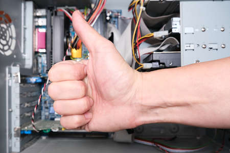 A repairer technician showing thumb up against disassembled computer system block.