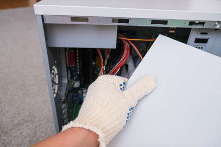 A technician in gloves opening cover of a system block of a broken computer in order to find a breakdown and repeir it. Reklamní fotografie