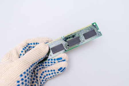 A hand of a repairer technician holding RAM, random access memory in order to upgrade an old computer against whote background, maintanance and repair concept.