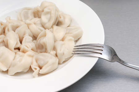 Traditional tasty boiled russian pelmeni, ravioli, dumplings with meat on white ceramic plate on gray background.