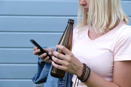 Relaxed woman with a bottle of beer, alcohol in hand and a smartphone, social problems and dependent behavior, weekend relaxation after work concept. Reklamní fotografie