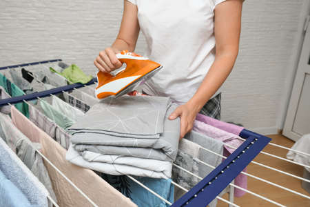 Unrecognizable woman collecting dry clean clothes from a drying rack and putting it in stack for ironing.