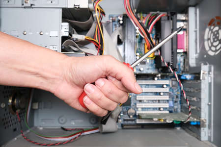 A hand of a technician repairer holding a screwdriver in order to upgrade or repair a broken home computer. Фото со стока