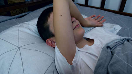 A boy lying in bed at night and turning from one side to the other in order to fall asleep, restless sleep and insomnia concept. Reklamní fotografie
