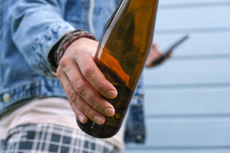 A brown bottle of beer in a hand of punk, informal woman, alcohol addiction, overdosage and abuse concept.