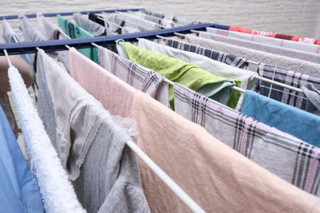 Fresh washed linen, clothes hanging on a dryer, dry apparel on a folding portable dryer close up, housekeeping, homework and chores concept.