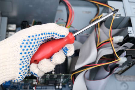 A hand of a technician repairer holding a screwdriver in order to upgrade or repair a broken home computer.