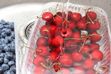 Washing ripe sweet cherry and blueberry in a kitchen sink under water jet, cleaning fresh juicy fruits in plastic containers of bacteria and dirt.