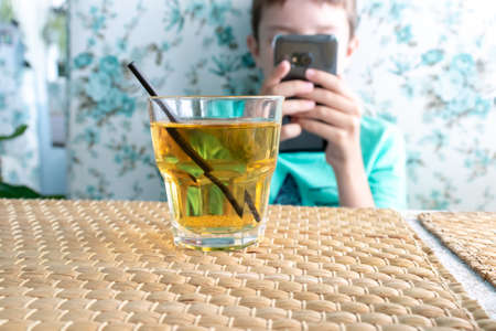A glass of juice with a straw on a table in front of a boy playing games on smartphone in a restaurant.