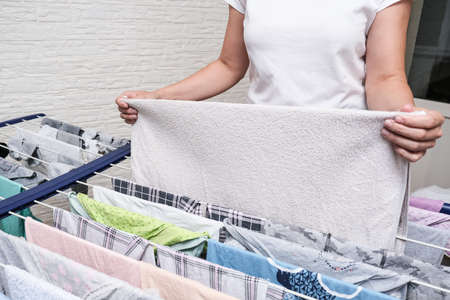 Unrecognizable woman collecting dry clean clothes, linen and towels from a drying rack and putting it in stack for ironing.