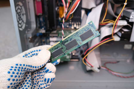 A hand of a repairer technician holding RAM, random access memory in order to upgrade an old computer, maintanance and repair concept.
