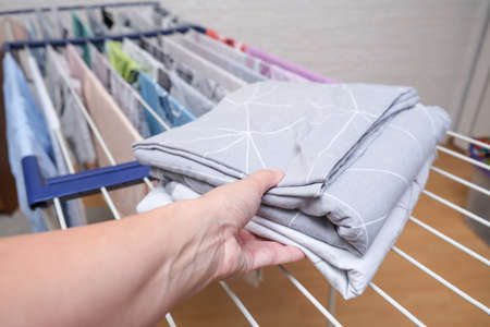 Hand holding fresh washed bed linen stacked, piled on a dryer, dry apparel on a folding portable dryer close up, housekeeping, homework and chores concept.