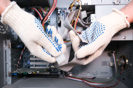 A technician in gloves holding cables of a broken computer in order to find a breakdown. Reklamní fotografie