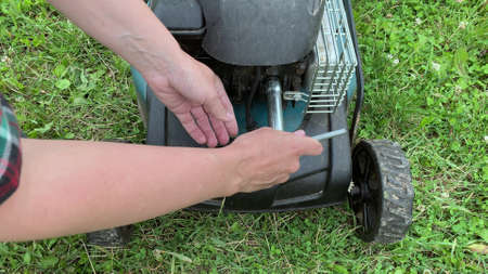 Changing replacing lawn mower spark plug, landscape equipment repair service, process of unscrewing spark plug. Reklamní fotografie