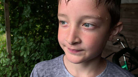A portrait of a boy with a raindrops on a face and wet hair after downpour, bad weather and storm in summer.