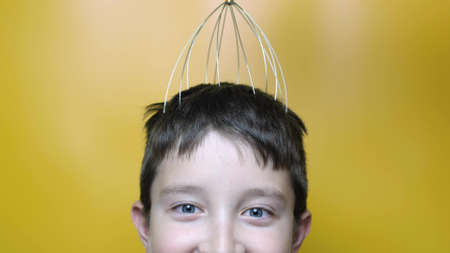 A caucasian boy enjoy head scalp massage by anti stress acupuncture metal octopus tool, equipment, she closes her eyes with pleasure, yellow background, close up view.