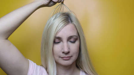 A caucasian blond woman enjoy head scalp massage by anti stress acupuncture metal octopus tool, equipment, she closes her eyes with pleasure, yellow background.