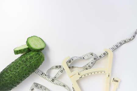 Fresh green sliced cucumber with a measuring tape and a caliper on white background as a concept of slimming diet and lose weight, copy space