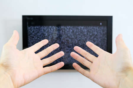 Hand of a perplexed person in front of the screen with white noise on it - tuning the television channels and connecting problems.