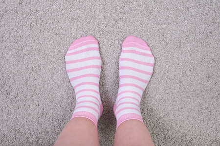 Woman female legs wearing pink and white striped plain cotton socks of classic style with elastic band standing on a cozy carpet at home