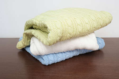 Stack of cozy comfortable homely clean washed knitted sweaters in pastel colors on a chest at home, table, laundry and washing clothes concept
