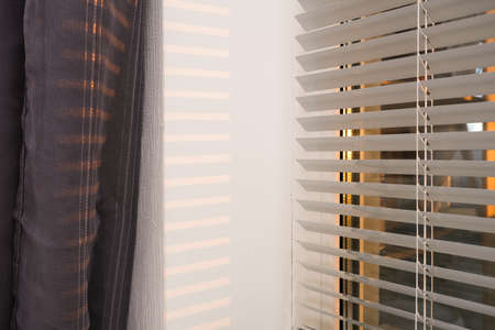 Blinds on a window in a bedroom with morning sun rays and beautiful light at waking up, getting up moment.