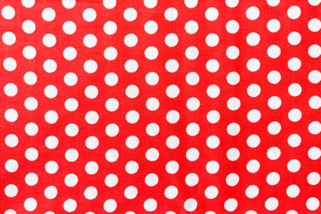 Polka dot on red canvas cotton texture, fabric background.